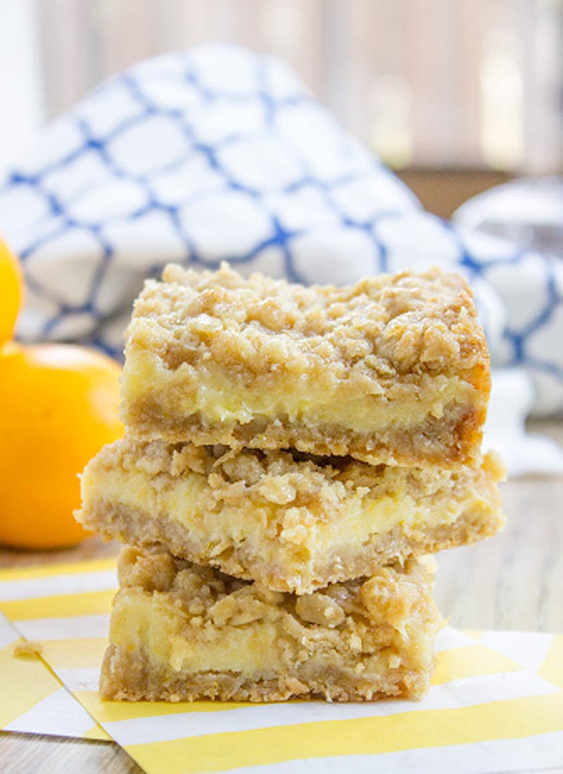 3 lemon crumb bars stacked on top of each other on a kitchen table
