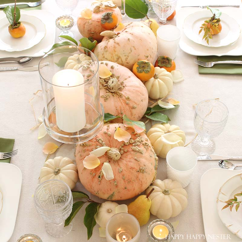 a collection of pink pumpkins on a white fall tablescapes