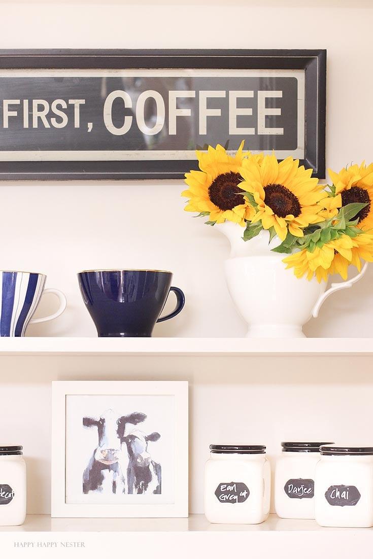Yellow sunflowers and coffee mugs on a white kitchen shelf