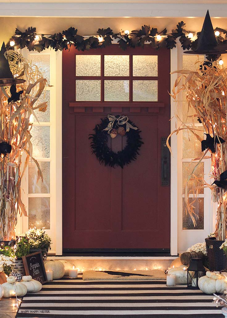 front red door with black feather wreath and white pumpkins on the ground. This a post about inexpensive Halloween front porch ideas