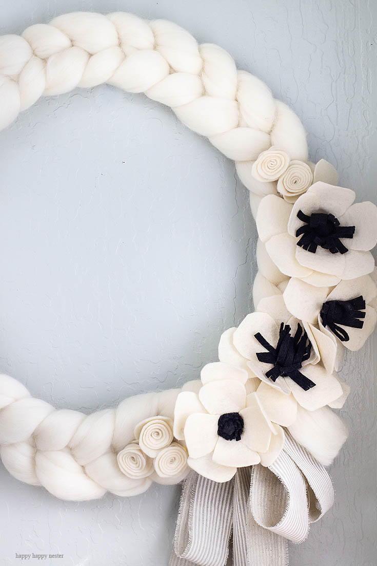 This white wreath is the perfect thing to brighten your home. Here is a quick and easy arm knitted wreath to chase your winter blues away! This wreath is so easy to arm knit, and you'll seriously love the results. I love how this bright wreath will look great all year long. Crafts   Arm Knit   Arm Knit Wreath   Wreaths   Wreath DIY   Craft Tutorial   Arm Knit Project   Wreath