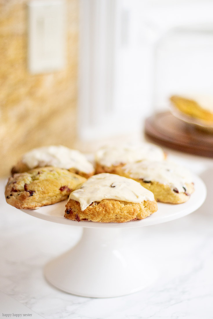 Need some helpful tips on how to bake a perfect flaky scone? Well this Fresh Orange Scone Recipe is the perfect blend of orange and cranberries and a creamy, moist dough. Cold shredded butter and minimal handling of the dough is the key to a fluffy English scone. Orange zest and juice is a delicious pair to cranberries. #baking #scones #joannagaines #favoriterecipes #englishscones